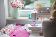 Sewing room with sewing machine, fabric, flowers and wom Royalty Free Stock Photography
