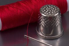 Sewing's objects. Needle, red thread and thimble Royalty Free Stock Photo