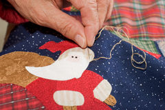 Sewing santa's brim. Quilter embroidering santa's brim in place Royalty Free Stock Photography