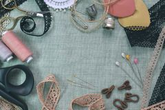 Sewing scene table flat lay composition. Threads, lace, pins, scissors, tape, reel, cloth. Pastel colors linen fabric. Text space. Top view banner template stock image