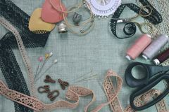 Sewing scene table flat lay composition. Threads, lace, pins, scissors, tape, reel, cloth. Pastel colors linen fabric. Text space. Top view banner template royalty free stock photography