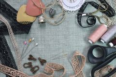 Sewing scene table flat lay composition. Threads, lace, pins, scissors, tape, reel, cloth. Pastel colors linen fabric. Text space. Top view banner template stock photography