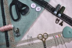 Sewing scene table flat lay composition. Threads, lace, pins, scissors, tape, reel, cloth. Pastel colors rose pink light stock photos