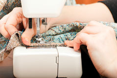 Sewing on a sewing machine. Female hands and part of the sewing machine Royalty Free Stock Image