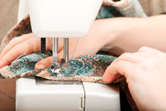 Sewing on a sewing machine. Female hands and part of the sewing machine Stock Images