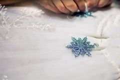 Sewing snowflakes on a dress for the holiday. Dress handmade. Fashionable design. Beautiful sewing flower. Designer work stock photography