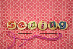 Sewing spelled in hand painted letters on buttons. On a vibrant textile background Royalty Free Stock Photography