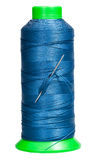 Sewing spool with blue thread and attached needle Royalty Free Stock Image