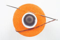 Sewing spool with a needle. Close up of orange sewing spool with a needle Royalty Free Stock Photo