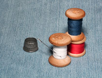 Sewing spools with colorful threads and needles, metal thimble l Stock Photos
