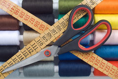 Sewing spools ,meter and scissors. Closeup of multicolored sewing spools ,meter and scissors Royalty Free Stock Images