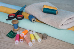 Sewing still life: colorful cloth. scissors and sewing kit includes threads of different colors, thimble and other sewing accessor Royalty Free Stock Photo