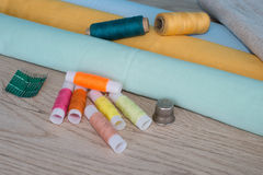 Sewing still life: colorful cloth. scissors and sewing kit includes threads of different colors, thimble and other sewing accessor Royalty Free Stock Image