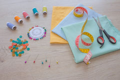 Sewing still life: colorful cloth. Sewing kit includes threads of different colors, thimble and other sewing accessories on table Stock Photo