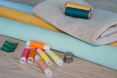 Sewing still life: colorful cloth. Sewing kit includes threads of different colors, thimble and other sewing accessories on wooden Royalty Free Stock Image
