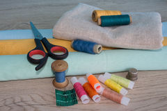 Sewing still life: colorful cloth. Sewing kit includes threads of different colors, thimble and other sewing accessories on wooden Stock Photography