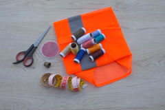 Sewing still life: colorful cloth. Sewing kit includes threads of different colors, thimble and other sewing accessories on wooden Stock Image