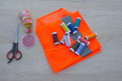 Sewing still life: colorful cloth. Sewing kit includes threads of different colors, thimble and other sewing accessories on wooden Stock Photo