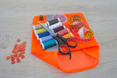 Sewing still life: colorful cloth. Sewing kit includes threads of different colors, thimble and other sewing accessories on wooden Royalty Free Stock Photography