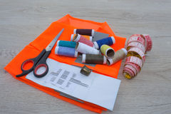 Sewing still life: colorful cloth. Sewing kit includes threads of different colors, thimble and other sewing accessories on wooden Stock Photos