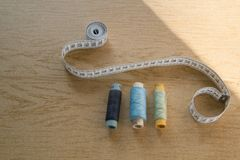 Sewing still life - different color cotton thread spools, thimble, needle, measuring tape. Top view stock photography