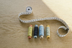 Sewing still life - different color cotton thread spools, thimble, needle, measuring tape. Top view stock images