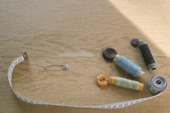 Sewing still life - multicolored cotton thread spools, thimble, needle, measuring tape. Top view stock images