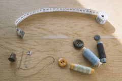 Sewing still life - multicolored cotton thread spools, thimble, needle, measuring tape. Top view royalty free stock photography