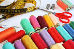 Sewing Stuff. Colourful spools of thread, pins, thimbles, scissors and measure tape on white background royalty free stock photos