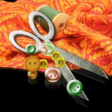 Sewing supplies. Scissors, buttons and spool of thread on a piece of colorful fabric stock images