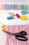 Sewing supplies - scissors, thread on fabric Royalty Free Stock Photography