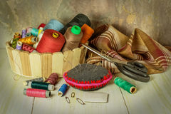 Sewing supplies. Thread spools in a basket, fabric, needles, chalk, scissors. Toned photo. Selective focus royalty free stock photo