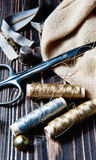Sewing textile or cloth. Scissors reel of thread, and golden fabric. Royalty Free Stock Images