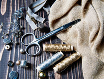 Sewing textile or cloth. Scissors reel of thread, and golden fabric. Royalty Free Stock Photo