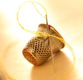 Sewing thimble and needle with thread Stock Photos