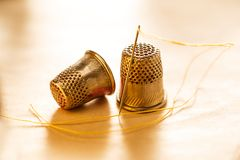 Sewing thimbles and needle with thread Royalty Free Stock Image