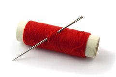 Sewing thread on bobbin. Red Bobbin with needle isolated on white Royalty Free Stock Photos