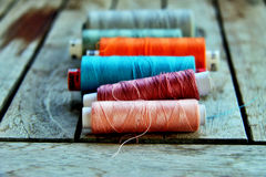 Sewing thread. In a bright and vibrant colors on a wooden table Stock Photo