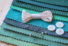 Sewing thread lies on different fabric patterns Royalty Free Stock Photo
