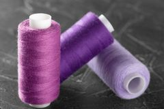 Sewing thread lilac color on the plastic coil. Object on a gray concrete background. Sewing thread on a bobbin of lilac color stock photo