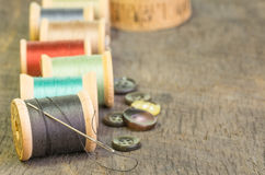Sewing thread with needle and buttons. Sewing thread on spools with needle and buttons Stock Photo