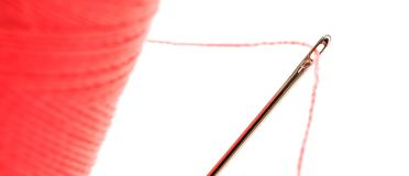 Sewing thread with needle. Isolated on a white background stock photography