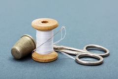 Sewing thread, needle, thimble and scissors Stock Photo