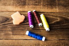 Sewing thread and needle on a wooden background. A sewing thread and needle on a wooden background stock photos