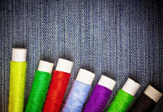 Sewing thread reels on blue denim Royalty Free Stock Image