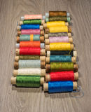 Sewing thread reels on a wood textured background. Bobbins of thread lined up in a row Royalty Free Stock Photography