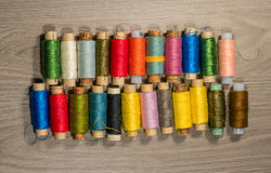 Sewing thread reels on a wood textured background. Bobbins of thread lined up in a row Royalty Free Stock Photos