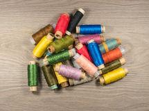 Sewing thread reels on a wood textured background. Stock Images