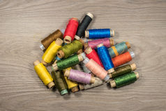 Sewing thread reels on a wood textured background. Bobbins of thread stacked pile Royalty Free Stock Images