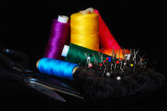 Sewing thread,scissors and thumbtacks. Set of sewing tools on the black background Royalty Free Stock Images